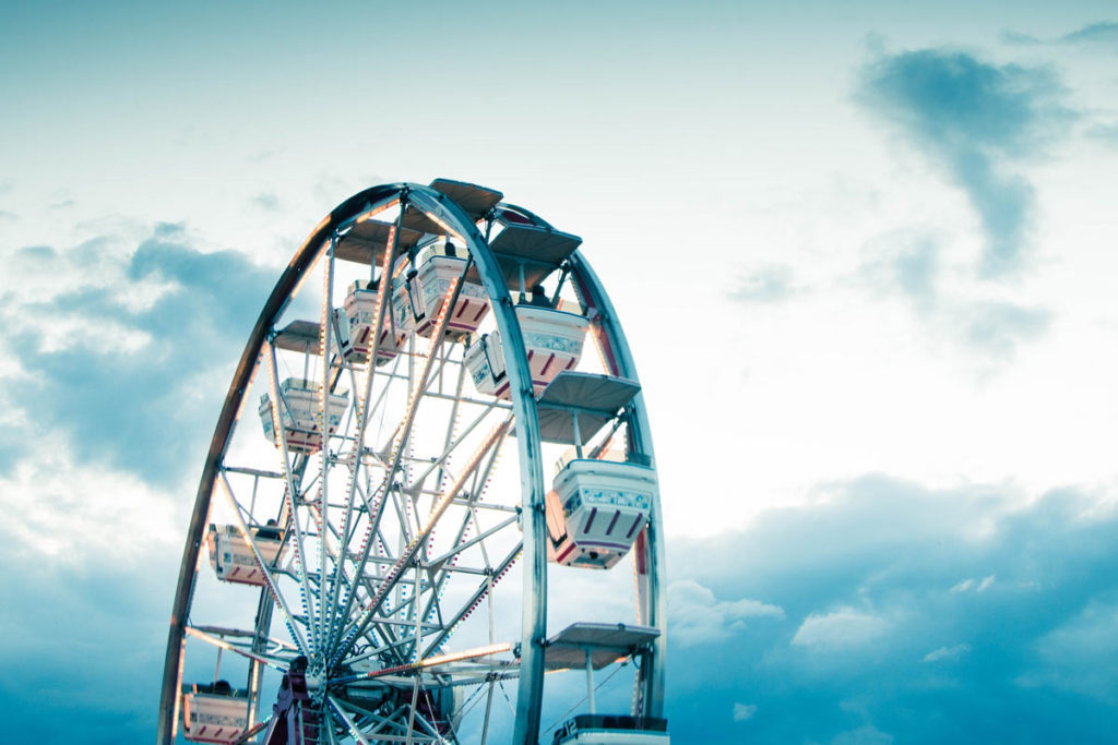 A ferris wheel with a background of cloudy blue sky
