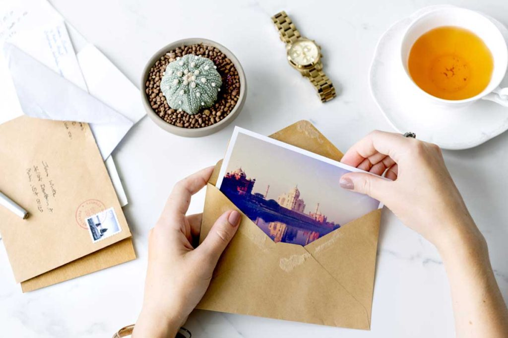 A person packs a personalized postcard in an envelope