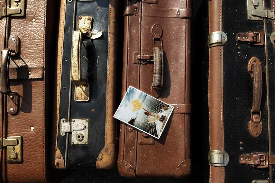 Vintage suitcase with a postcard on top.