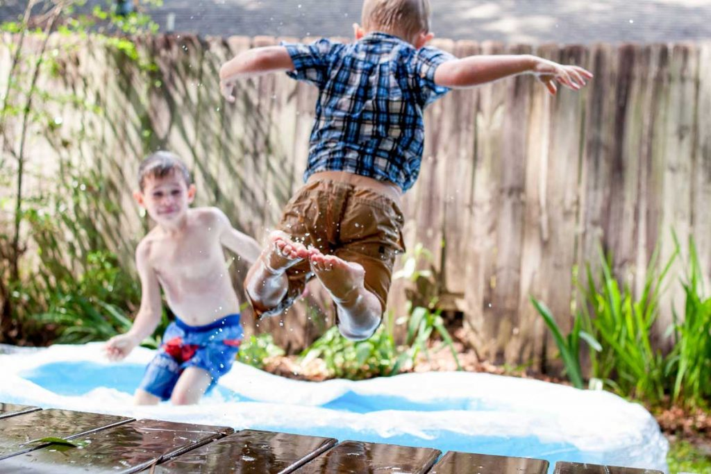 Two kids playing in the garden pool