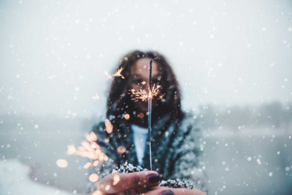 Woman holding a sparkler in the snowfall