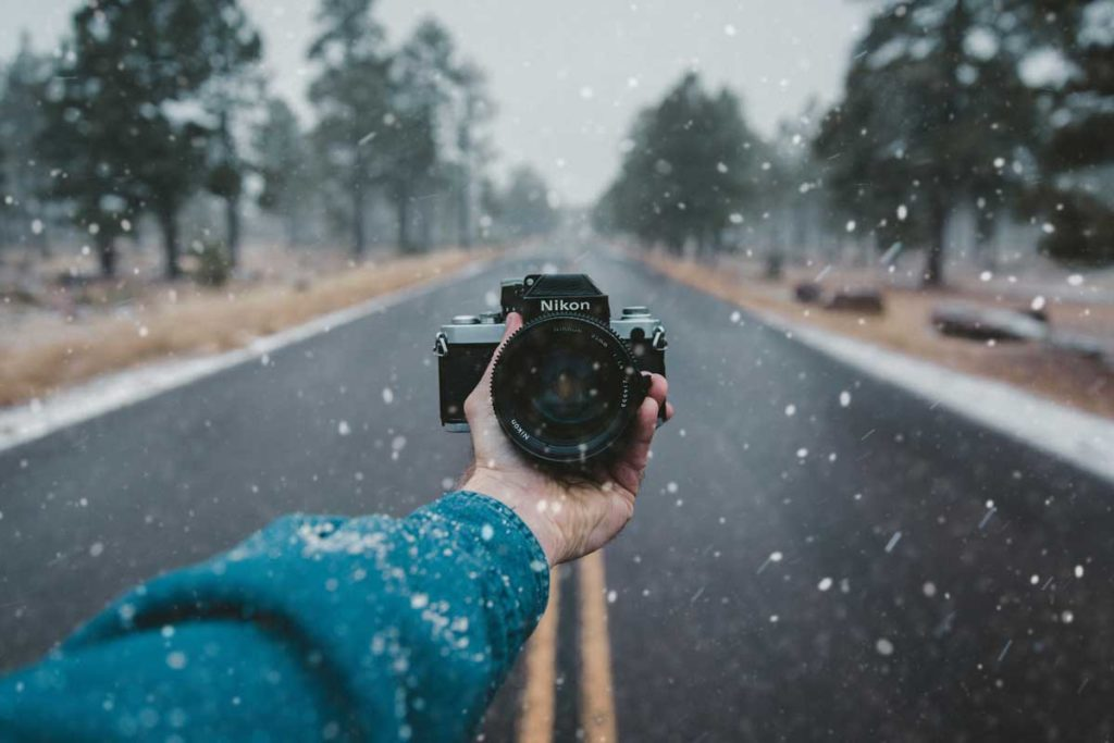 Hand holding a camera in the snowfall