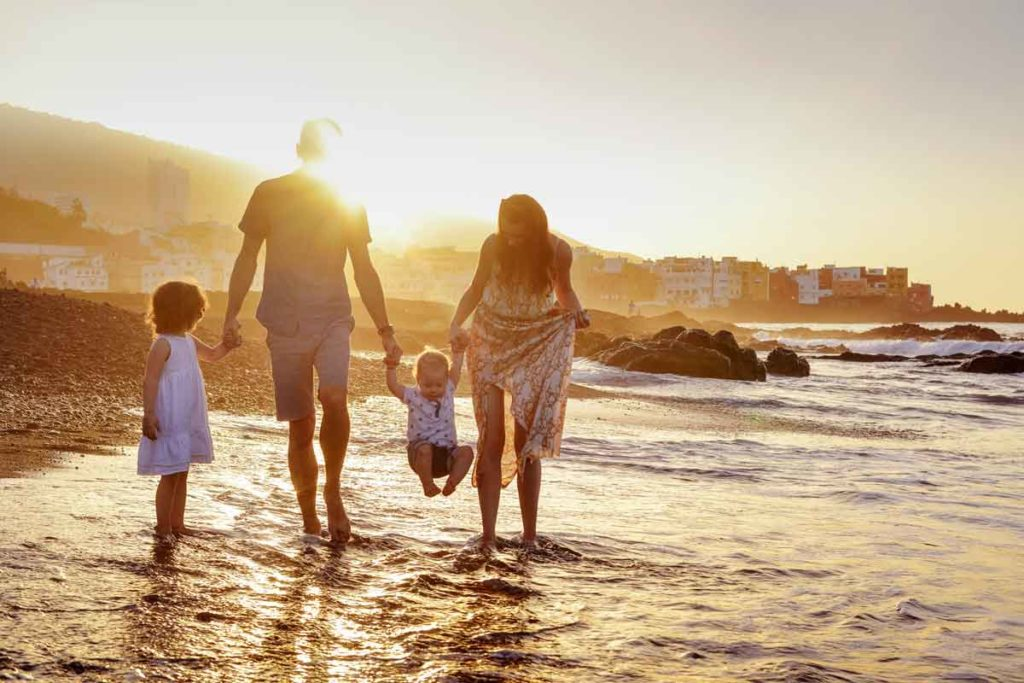 Family having a walk at the beach in sunset for perfect family portraits