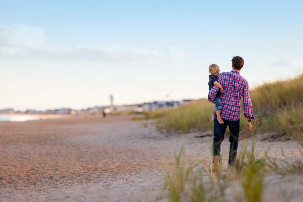 Father and child walking on the beach