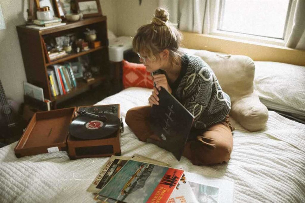 Woman sits on bed listening to a record