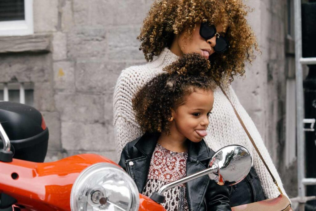 Mother and Daughter pose for a photo together next to a motorbike