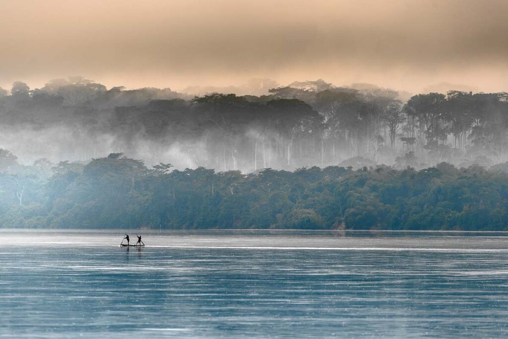 A foggy day in the Congo over a lake surrounded by trees