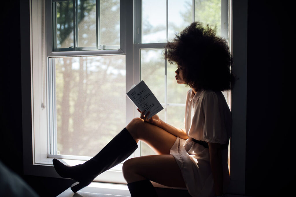 Woman sits reading one top travel books to read in window