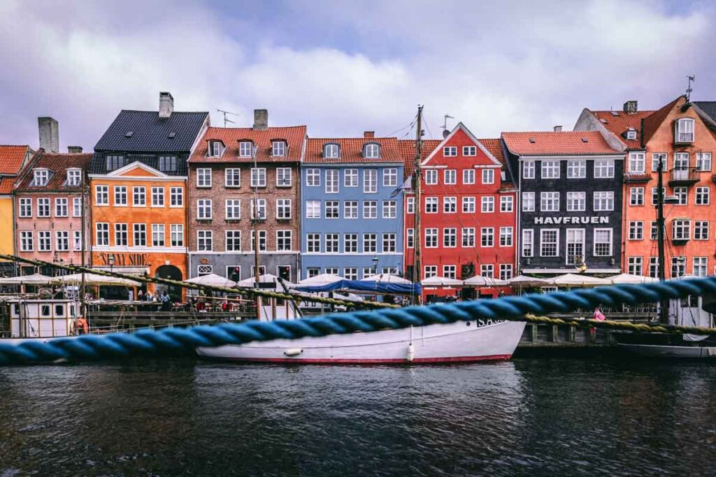 A row of colorful houses before a river from the setting of this must-read