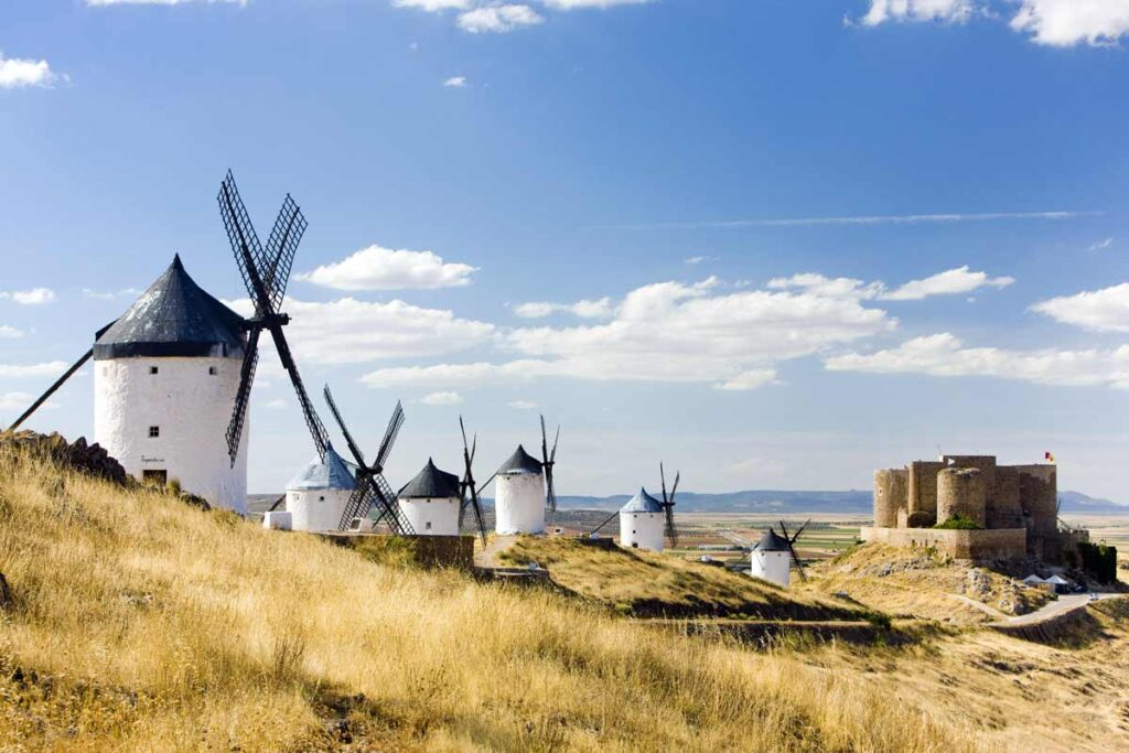 A trail of old windmills in front of a castle