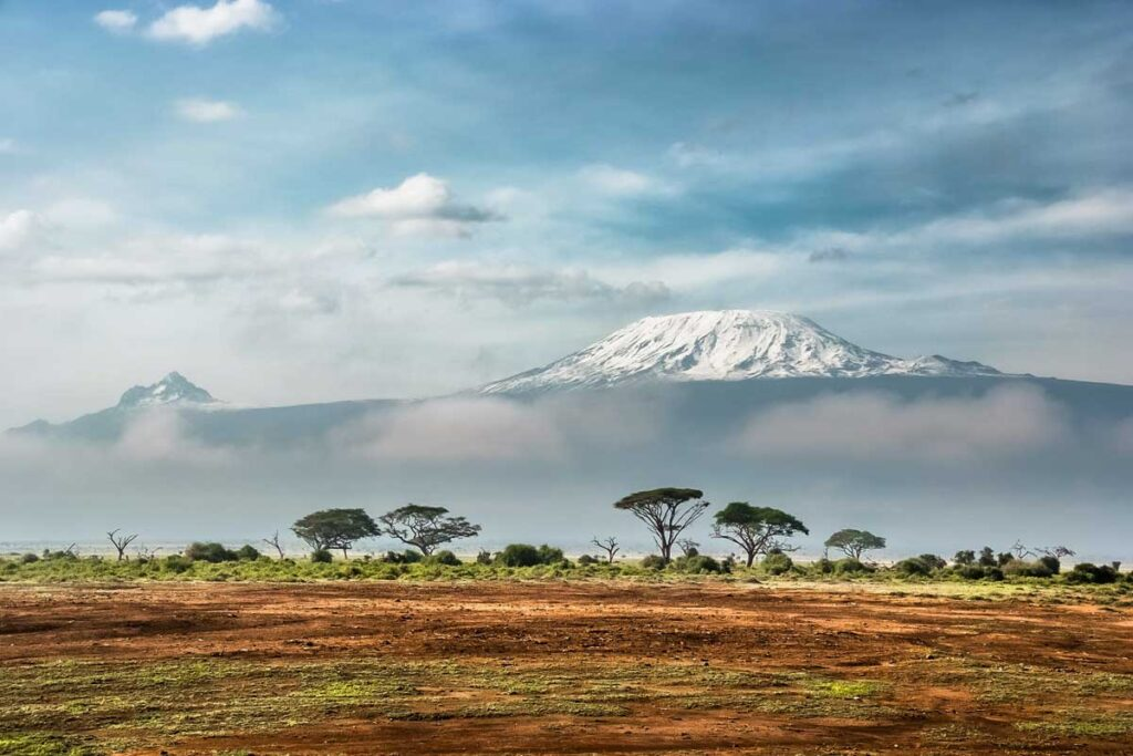 A safari in Africa lies in front of cloudy mountains
