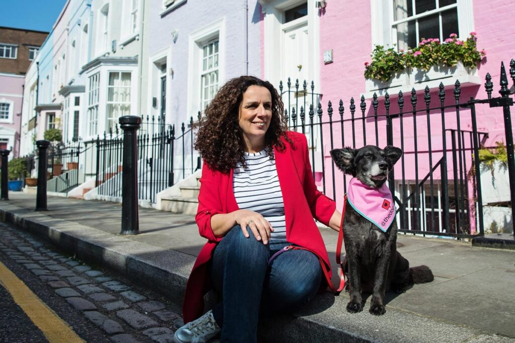 Woman sits next to dog on colorful street