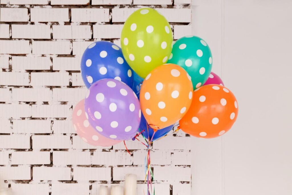 Colorful ballons in front of white brick wall celebrate long distance birthday