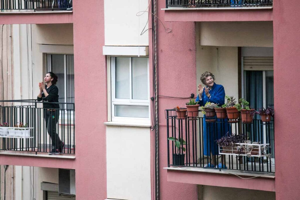 Two women clap from their balconies in pink houses