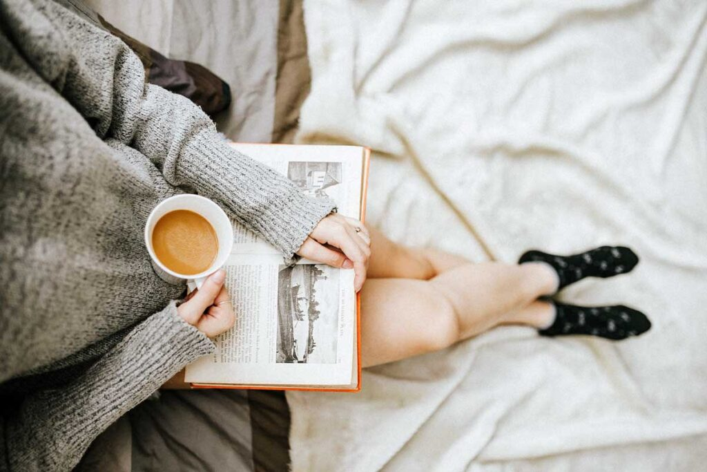 Woman with tea reads a book on staycation