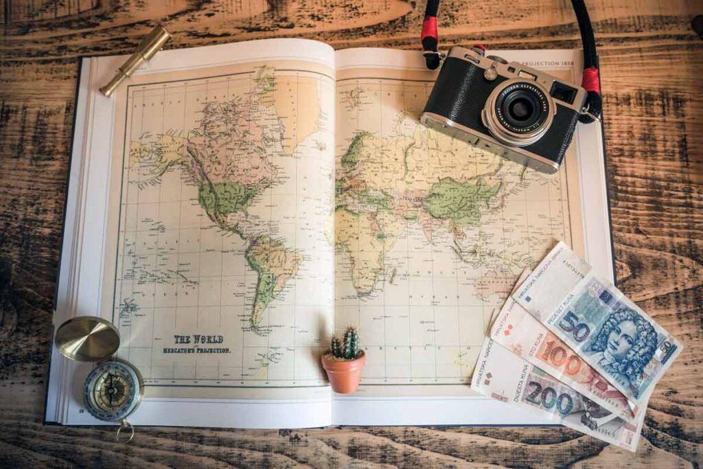 A map lies on the table with camera, money and compass