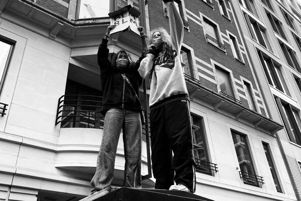 Two protestors stand together on a roof during BLM protests