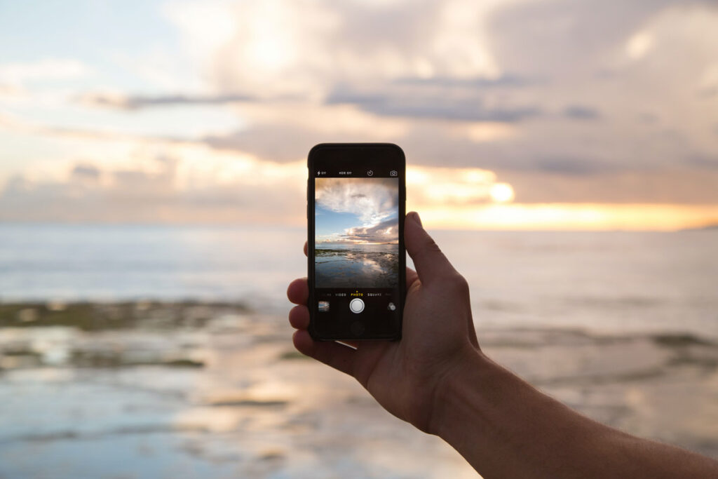 A person photographs the sea with his phone