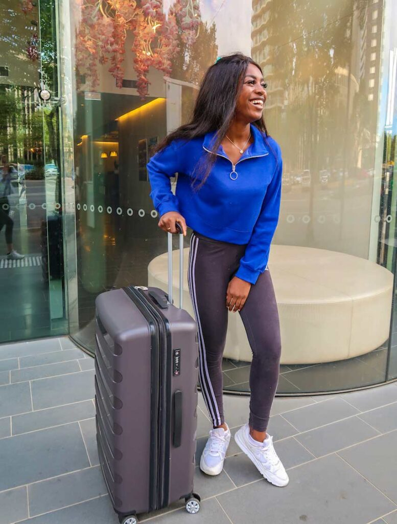 Efia stands with a suitcase disproving at leat one implicit racial microaggression
