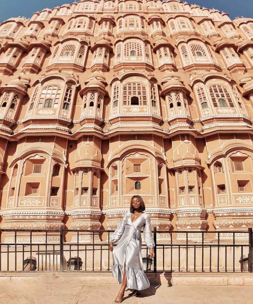 Jessica stands before an impressive building while traveling black