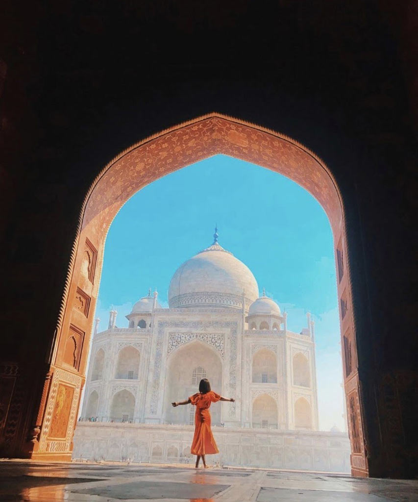 Jessica dances under an arch with a palace behind