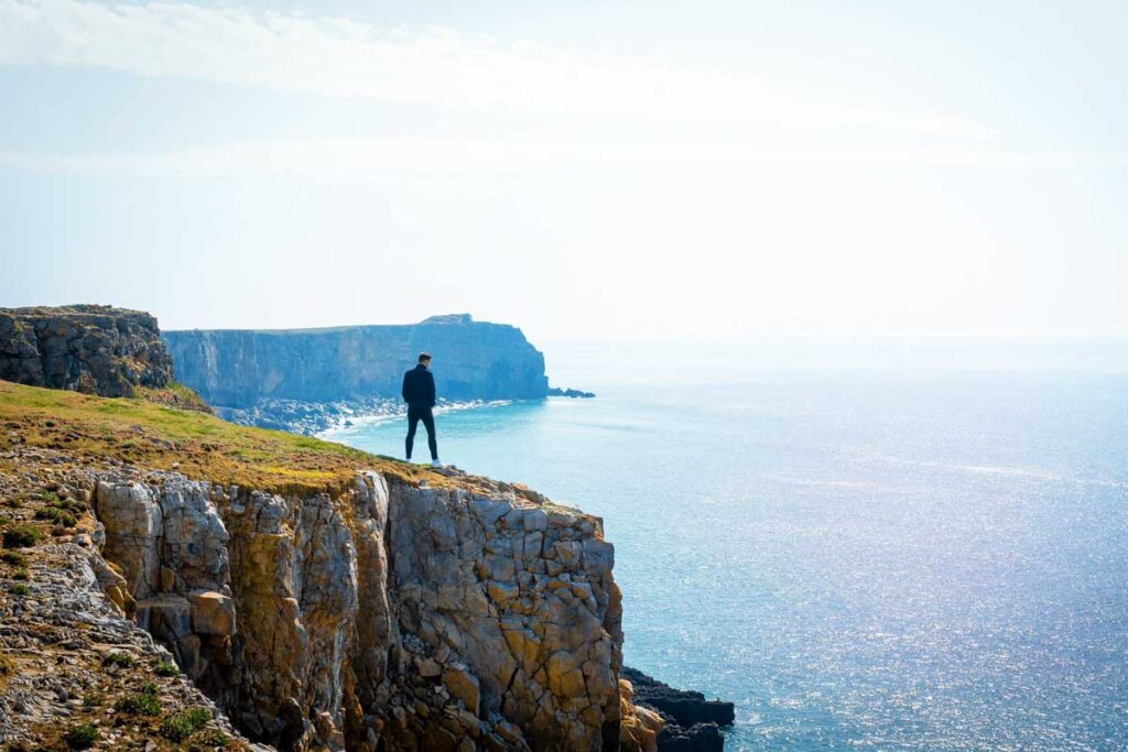 A man stands on the White Cliffs of Dover in the distance