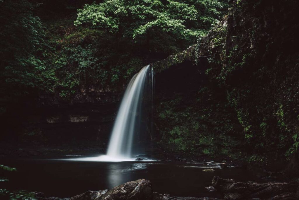 A waterfall at the Brecon Beacons in the darkness deserves a spot as one of the best rural places to visit in the UK.