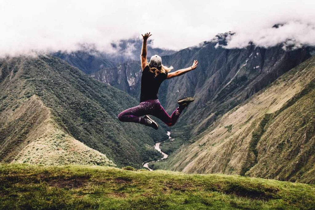A solo woman traveller from one of our top travel Instagram accounts leaps for joy in the valleys