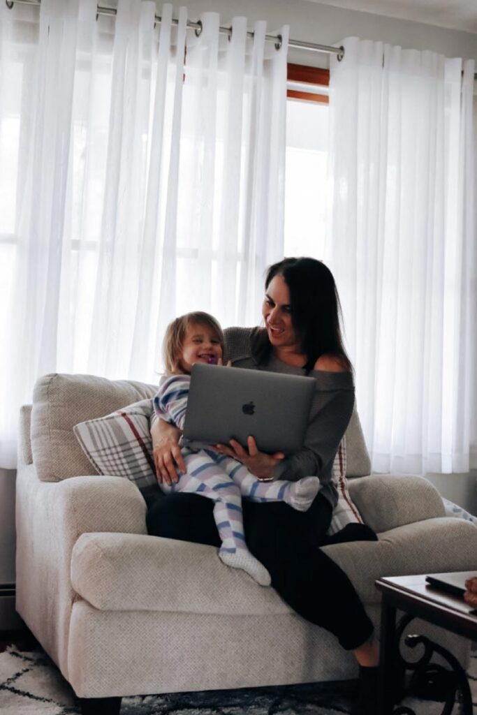 Mother and todler laugh at something on the laptop