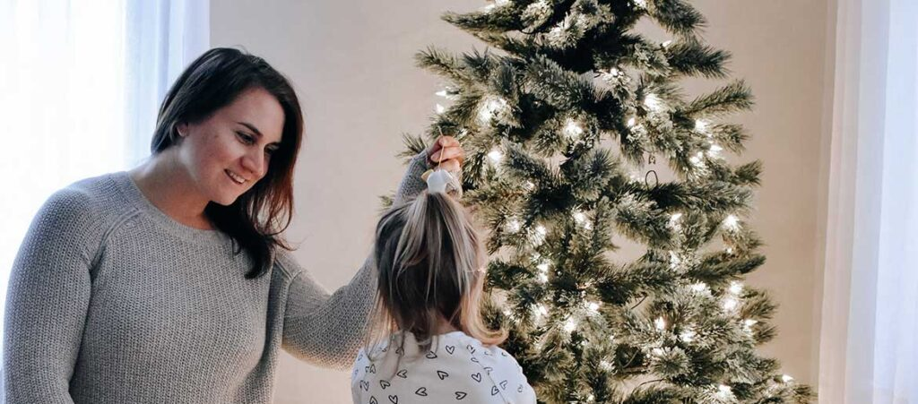 A mother and her daughter get festive decorating their Christmas tree
