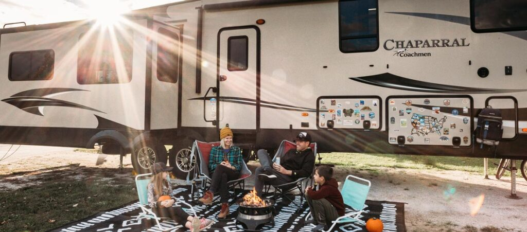 A family sitting around a fire place in front of their RV home