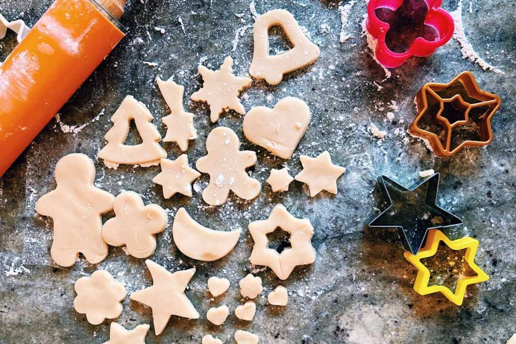 Easy Christmas baking crafts shown here are cut out raw biscuits in Christmas shapes