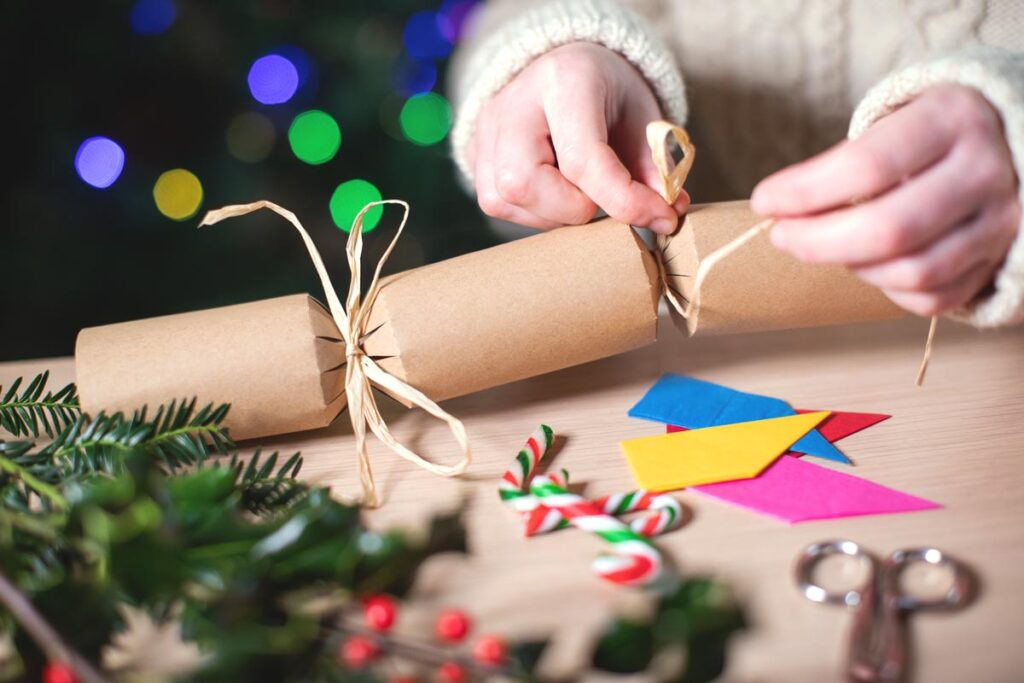 A DIY Christmas cracker being tied with string