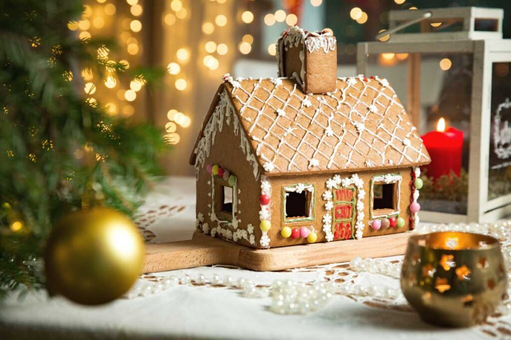 Decorated Gingerbread house in front of Christmas decorations
