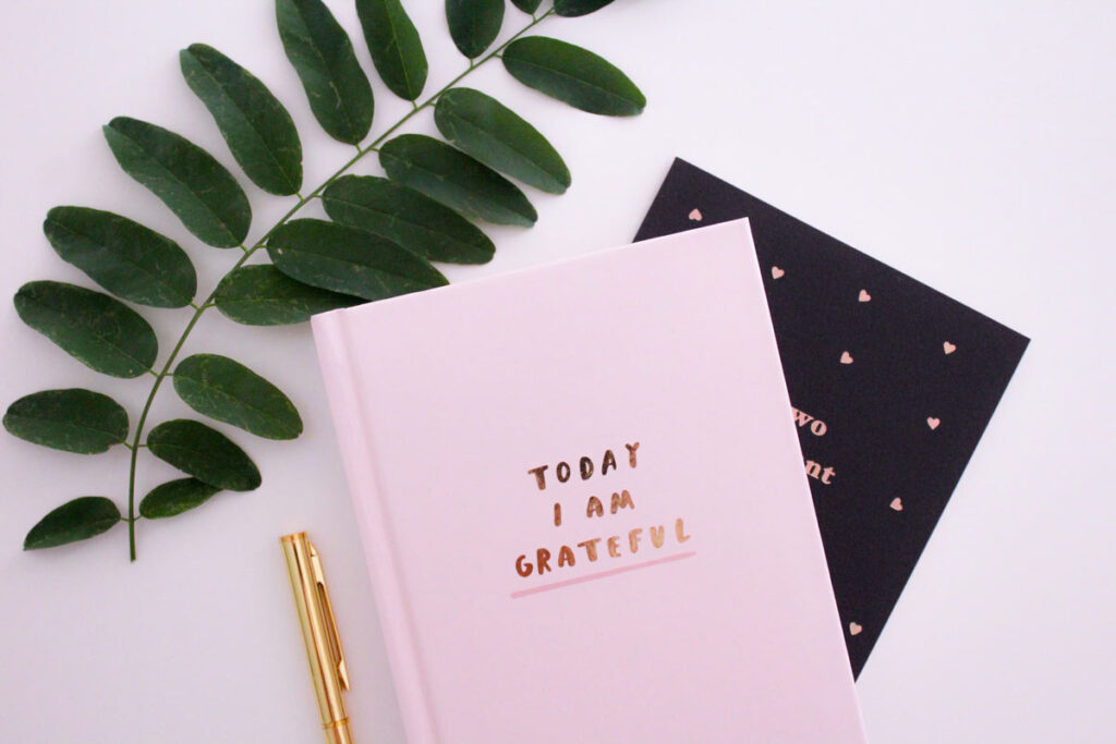 A positive message on a diary next to plants and pens