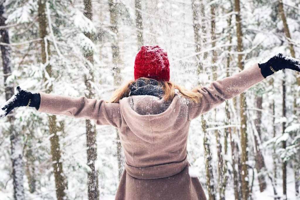 A woman throws her arms open in the snow to welcome the new year