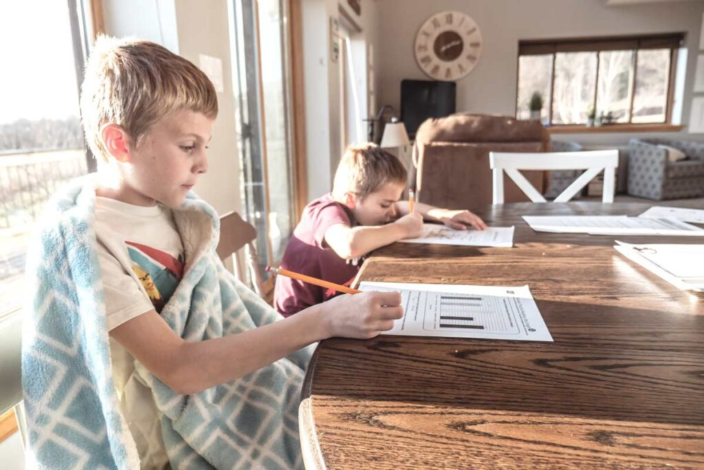 Two kids sit do homework as part of their New Year's Resolutions ideas