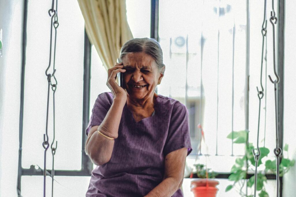 An old woman laughs on the phone
