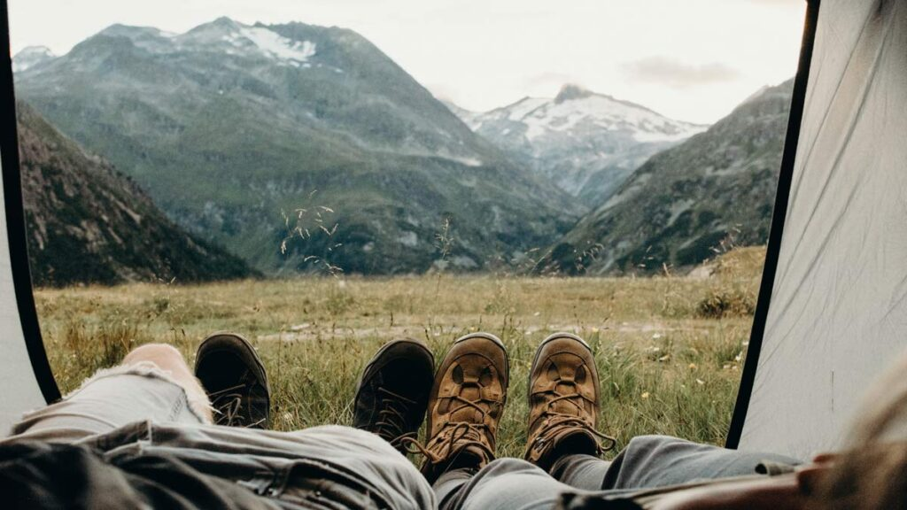 Camping bloggers lie in a tent with their feet sticking out with mountainous foreground
