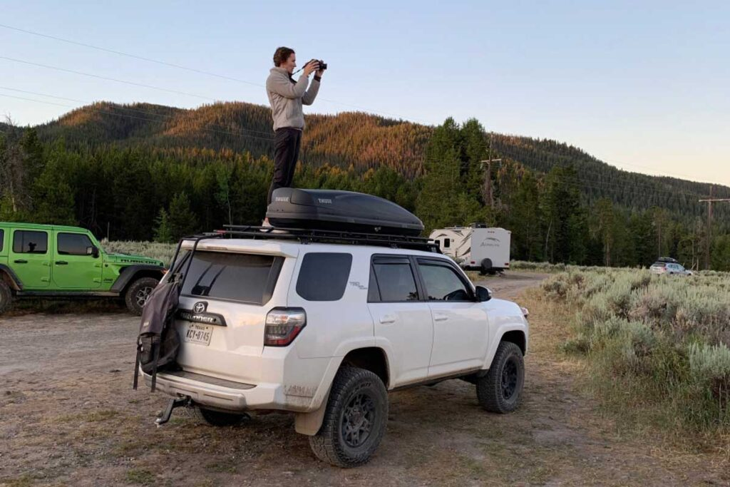 Cass from Tails of Wanderlust camping blog stands on car roof with a camera