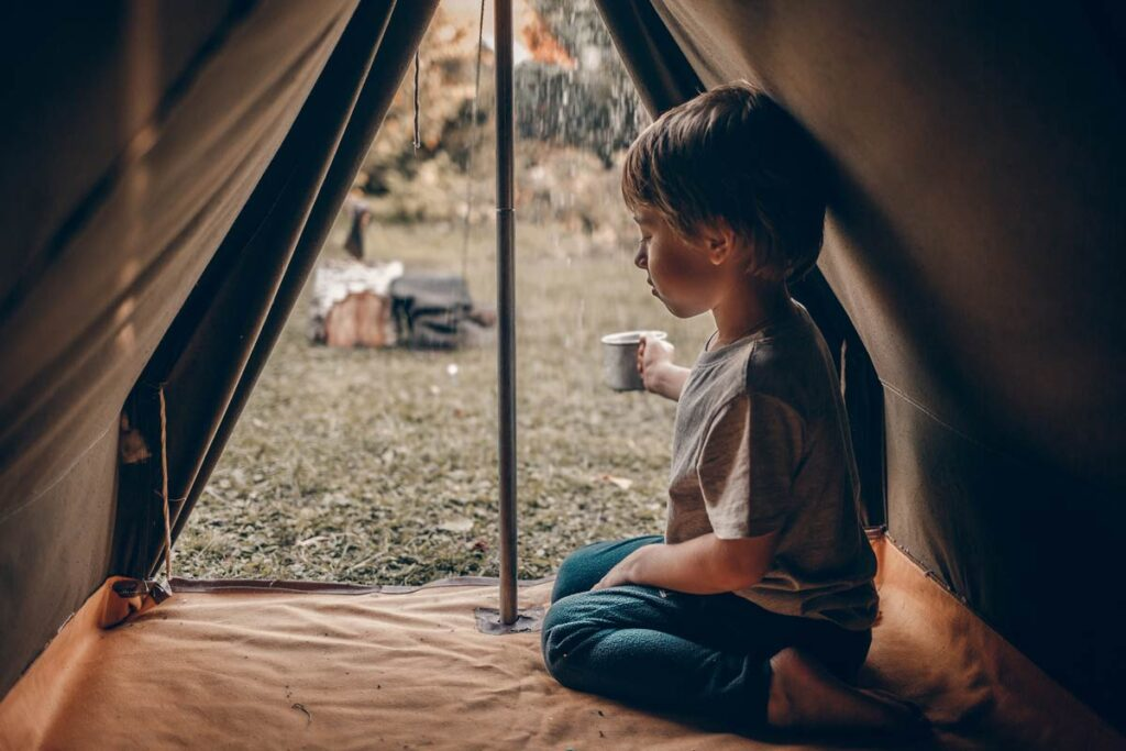 A little boys looks at the rain from inside his open tent
