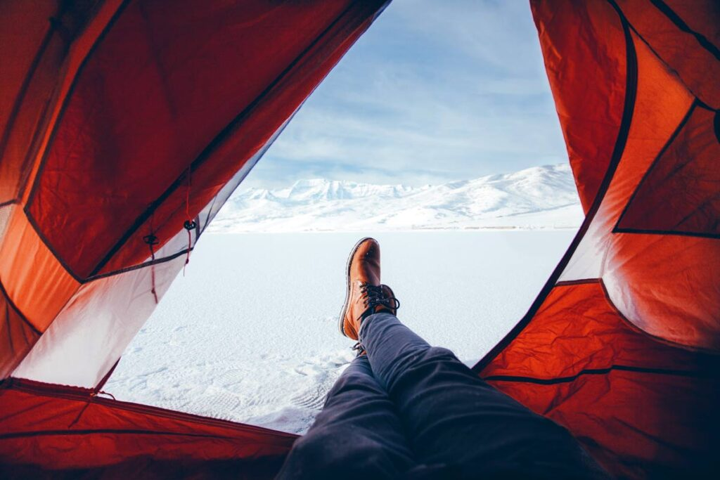 Tentporn of man with feed hanging out of tent towards snowy view