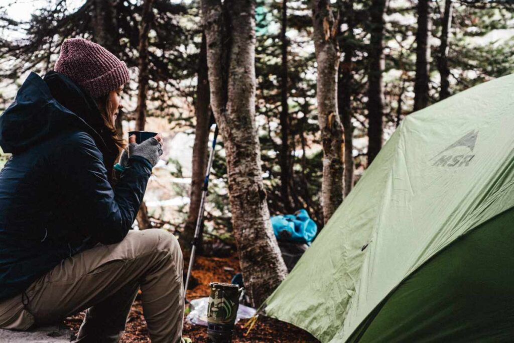 A woman sits near a tent with tea having followed easy camping hacks