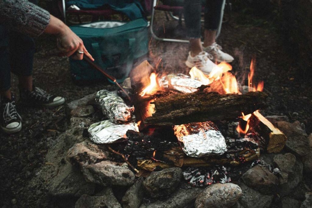 Foil-wrapped food on the fire is one of our easy camping hacks for food prep