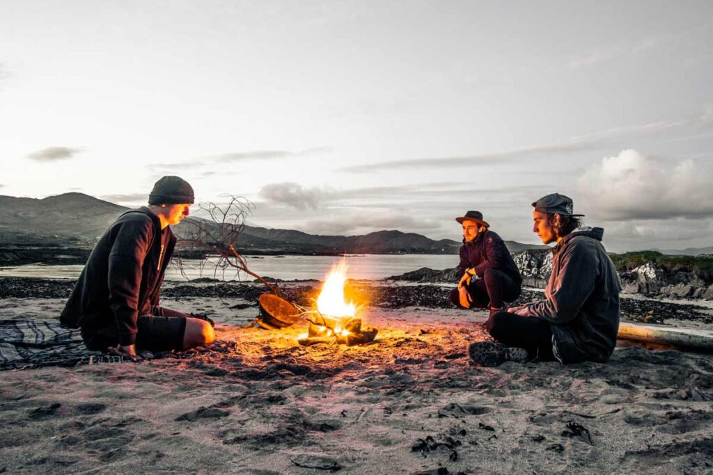 3 young people sit around a fire: a camping life hack to avoid insects