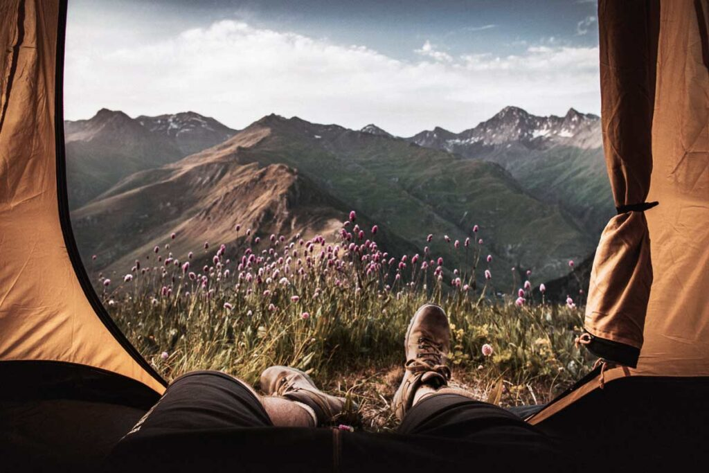 A camper's legs hang out of the tent showing a beautiful mountainous landscape