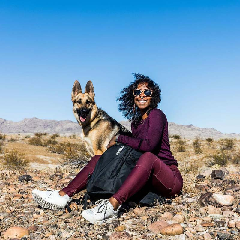 Black travel influencer Naomi sits on a jagged rock face with her dog