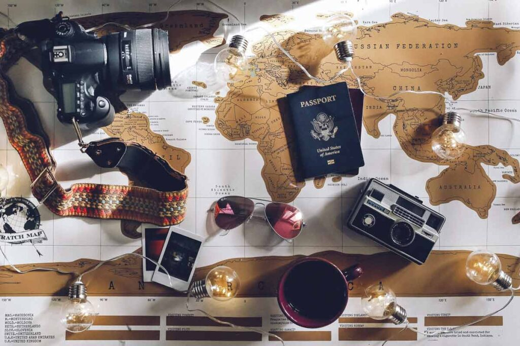 A world map flay lay with passports, photos and more to play your trip