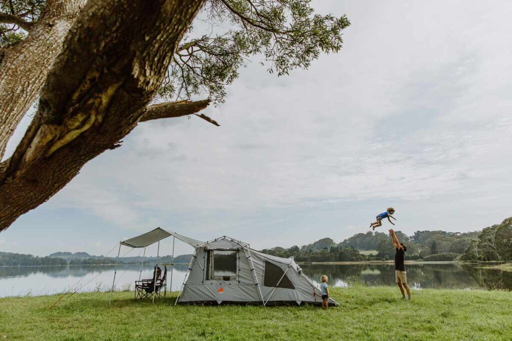 A father throws his little boy in the air next to the family tent on the lakeside
