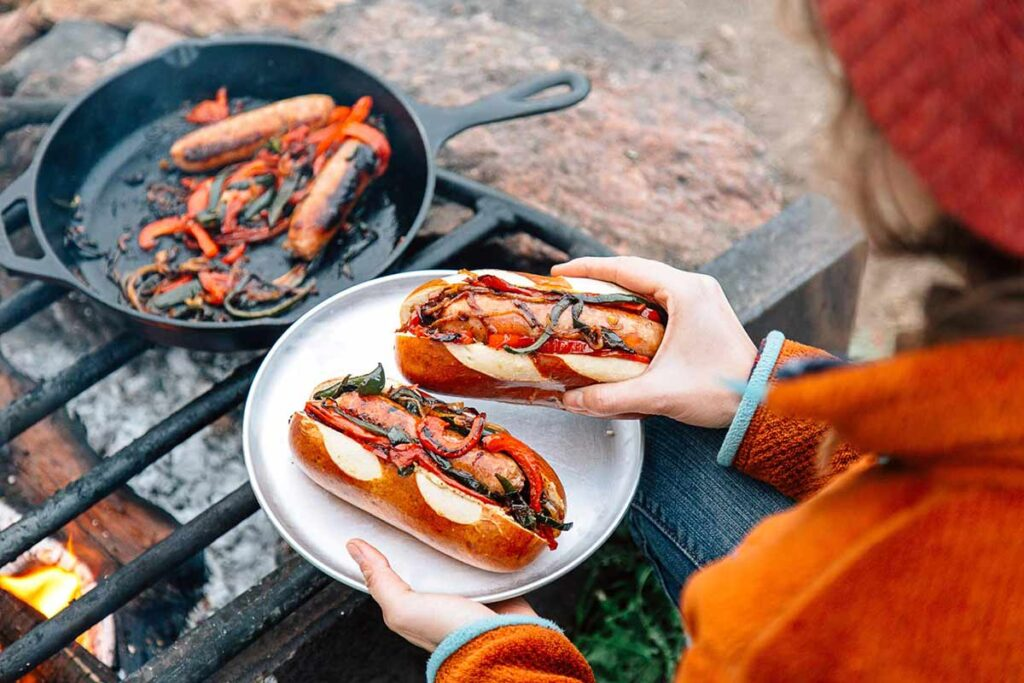 A woman holds a plate of hotdogs fresh from the camping grill